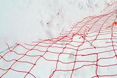 Damaged red yarn grid under white snow, winter season. — Stock Photo