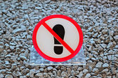 No footprints plastic sign on stone surface, modern security. — Stock Photo