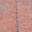 Long metal wire (lightning-conductor) on red brick wall, industrial. — Stock Photo