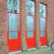 Red doors on the brick wall, building industry. — Stock Photo