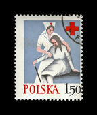 Nurse help old woman, Polish Red Cross.vintage post stamp isolated on black. — Stock Photo