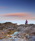 Guy is sitting on a rock by the sea — Stock Photo