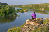 Man sits on a rock above the river  — Stock Photo