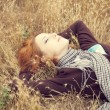 Young beautiful girl lying at yellow autumn field. — Stock Photo #12430749
