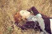 Młode piękne dziewczyny leżącej w żółtym polu jesień. — Zdjęcie stockowe