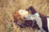 Young beautiful girl lying at yellow autumn field. — Zdjęcie stockowe
