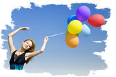 Redhead girl with colour balloons at blue sky background. — Stockfoto