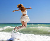 Young redhead girl jumping at the beach. — Stock Photo