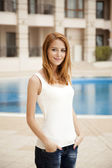 Redhead girl near pool in hotel. — Stockfoto
