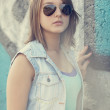 Teen girl in sunglasses near graffiti wall. — Stock Photo #13526499