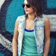 Teen girl in sunglasses near graffiti wall. — 图库照片
