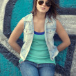 Teen girl in sunglasses near graffiti wall. — Stock fotografie