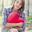Sad teen girl with heart sitting at railway. — Stockfoto