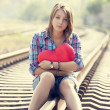 Photo: Sad teen girl with heart sitting at railway.