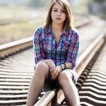 Sad teen girl sitting at railway. — Stock Photo