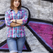 Photo: Style teen girl standing near graffiti wall.