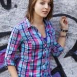 Style teen girl standing near graffiti wall. — Stock Photo