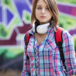Style teen girl with backpack standing near graffiti wall. — 图库照片 #13526523