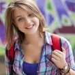 Stock Photo: Style teen girl with backpack standing near graffiti wall.