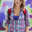 Style teen girl with backpack standing near graffiti wall. — Photo