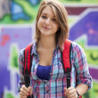 Style teen girl with backpack standing near graffiti wall. — Stockfoto