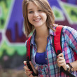 Photo: Style teen girl with backpack standing near graffiti wall.