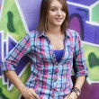 Style teen girl standing near graffiti wall. — Stock Photo