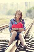 Sad teen girl with heart sitting at railway. — Stock Photo
