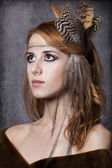 Style redhead girl with feathers on the head. Studio shot. — Stock Photo
