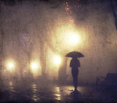 Single girl with umbrella at night alley. Photo with noise. — Stock Photo