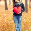 Redhead girl with toy heart at autumn park. - Stock Photo