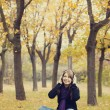 Young fashion girl with headphones at autumn park. - Stock Photo