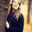Portrait of girl with headphones at outdoor. Autumn. - Stock Photo