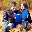 Beautiful couple with notebook at autumn park. — Stock Photo
