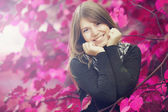 Beautiful girl at autumn park. Leafs in pink color. — Stock Photo
