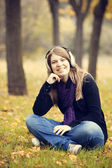 Young fashion girl with headphones at autumn park. — Stock Photo
