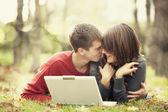 Beautiful couple with laptop at autumn park. — Stock Photo