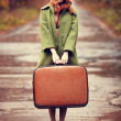 Style redhead girl with suitcase at beautiful autumn alley. — Stock Photo #14283653