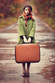 Style redhead girl with suitcase at beautiful autumn alley. — Stock Photo