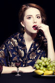 Portrait of beautiful rich women with grapes. — Stock Photo