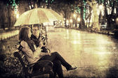 Couple sititng at bench in night lights. Photo in vintage multic — Stock Photo