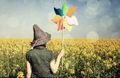 Girl with wind turbine at rapeseed field — Stock Photo