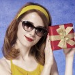 Royalty-Free Stock Photo: American redhead girl in sunglasses with gift.