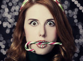 Beautiful surprised women with Christmas candy. — Stock Photo