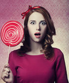 Beautiful redhead girl with lollipop. Photo in retro style. — Stock Photo