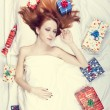 Redhead girl in bed with gifts. Photo in warm tone style. — Stock Photo #16645501