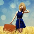 Redhead girl with suitcase at spring wheat field. — Stock Photo #16689157