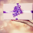 Female hand holding gift. — Stock Photo