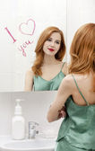 Redhead girl near mirror with heart it in bathroom. — Stock Photo