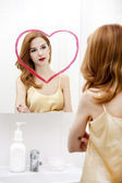 Redhead girl near mirror with heart it in bathroom. — Stock Photo